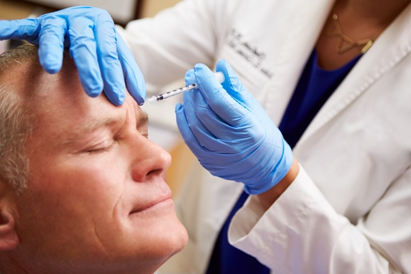 Middle-aged man getting cosmetic injection in forehead | Botox for men and women
