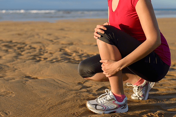 Woman grasping lower leg | Are you at risk for varicose veins?