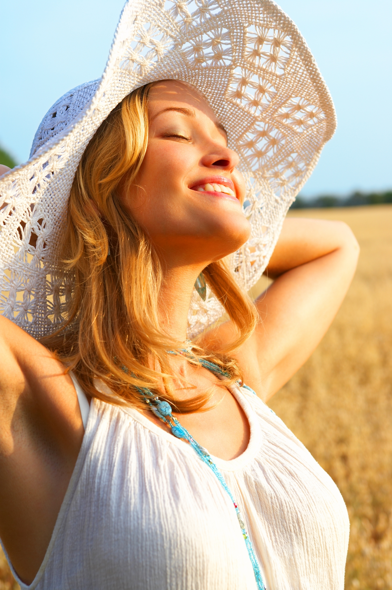 Woman standing in field wearing hat for protection from sun - Medical-grade sunscreen can help, too!